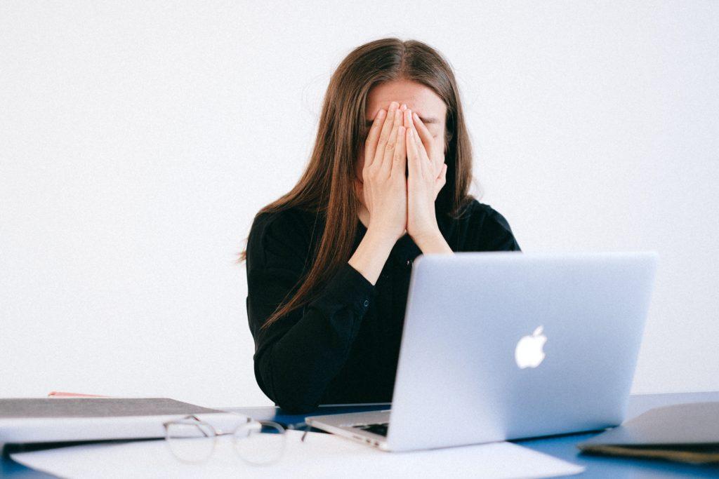 Frau sitzt am Laptop und hat eine Angststörung am Arbeitsplatz